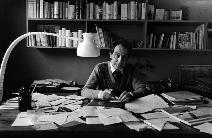 fotografia mostra Italo Calvino sentado em escrivaninha repleta de papeis, com estantes de livros na parede atrás