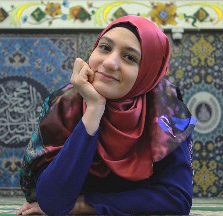 Fotografia de Fatima usando veu vermelho e diante de uma parede ornamentada com azulejos