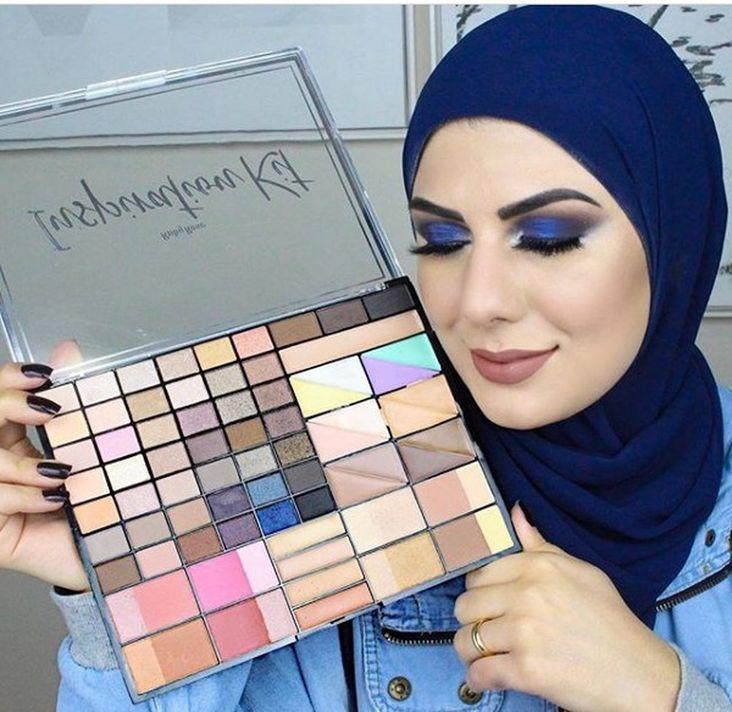 Fotografia de Mag usando lenço azul em volta do rosto, com olhos fechados e maquiados, mostrando uma paleta de sombras (maquiagem)